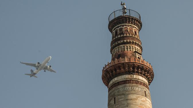 Pesawat terbang melintas dekat situs warisan dunia UNESCO Qutub Minar di New Delhi, India, Kamis (13/2/2020). Bangunan ini pernah diterjang bencana alam berkali-kali, namun tetap kokoh. (Xinhua/Javed Dar)