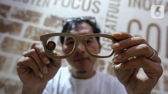 Pengrajin Yuyud, membuat kacamata dari limbah kayu di Jalan Salak, Pamulang, Tangerang Selatan, Senin (12/10/2020). Kacamata dari limbah kayu yang dijual dengan harga Rp 300 ribu hingga diatas Rp 1 juta dijual sesuai pesanan pembeli. (Liputan6.com/Fery Pradolo)