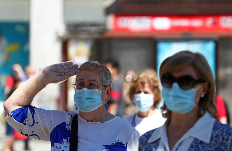 People hold a minute of silence in memory of those who died of the coronavirus disease (COVID-19), in Madrid