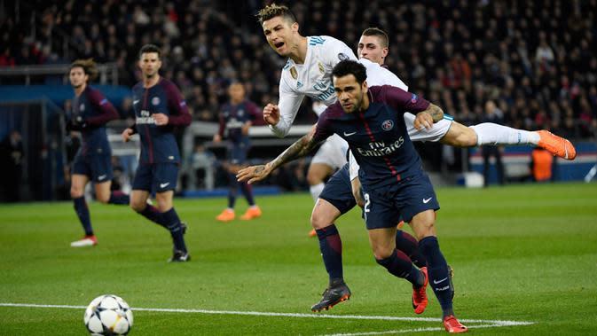 Bintang Real Madrid, Cristiano Ronaldo berebut bola dengan bek PSG, Dani Alves pada laga Liga Champions di Stadion Parc des Princes, Paris, Selasa (6/3/2018). PSG kalah agregat 2-5 dari Madrid. (AFP/Christophe Simon)