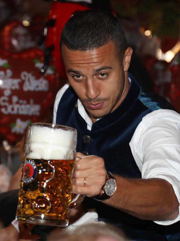 Gelandang Bayern Munchen, Thiago Alcantara berpose dengan bir selama kunjungan tahunan klub sepak bola di festival bir Oktoberfest di Munich, Jerman selatan pada 6 Oktober 2019. (AFP.Stefan Matzke)