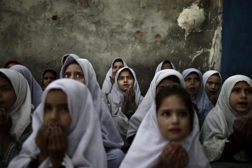 In this Thursday, Jan. 3, 2013 photo, Pakistani schoolgirls, who were displaced with their families from Pakistan's tribal areas due to fighting between militants and the army, chant prayers during a class to pay tribute for five female teachers and two aid workers who were killed by gunmen, at a school, on the outskirts of Islamabad, Pakistan. Wonder Woman and Supergirl now have a Pakistani counterpart in the pantheon of female superheroes _ one who shows a lot less skin. Meet Burka Avenger: a mild-mannered teacher with secret martial arts skills who uses a flowing black burka to hide her identity as she fights local thugs seeking to shut down the girls' school where she works. Sadly, it's a battle Pakistanis are all too familiar with in the real world.(AP Photo/Muhammed Muheisen)