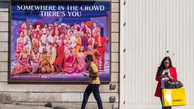 Orang-orang berjalan melewati sebuah reklame di West End, London, Inggris, pada 21 September 2020. Menteri Kesehatan Matt Hancock pada Minggu (20/9) mengatakan Inggris sedang menghadapi