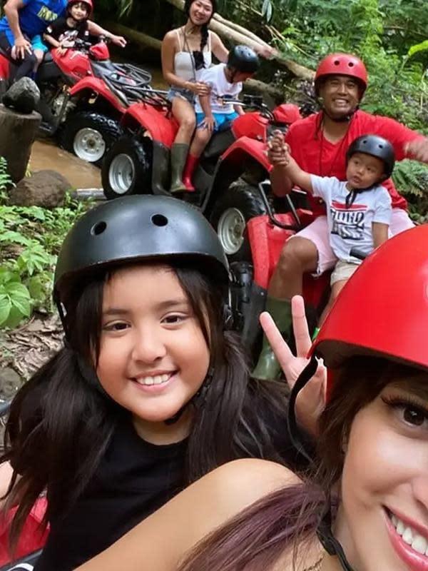 Potret bahagia Nia Ramadhani bersama suami dan anak-anaknya ketika mengendarai motor All Terrain Vehicle (ATV). Terlihat keseruan ketika melihat medan yang dilewati ada kali dan bukit dengan pemandangan hijau disekelilingnya. (Instagram/ramadhaniabakrie)