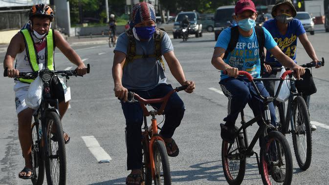 Pekerja mengendarai sepeda untuk pulang ke rumah di Manila pada 20 Mei 2020. Penjualan sepeda meroket menyentuh 300-500 unit dalam dua hari sejak pemerintah Filipina mulai melonggarkan langkah-langkah karantina yang dilakukan untuk mencegah penyebaran pandemi COVID-19. (Ted ALJIBE/AFP)