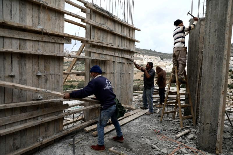 Palestinian Labourers work at a construction site in the Israeli settlement of Ramat Givat Zeev in the Israeli-occupied West Bank
