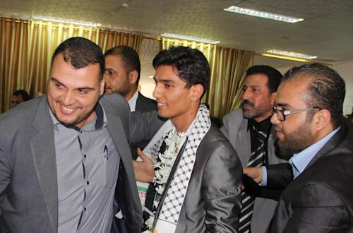 Arab Idol winner Palestinian Mohammed Assaf, center, arrives at the Rafah crossing point on the border between Egypt and the southern Gaza Strip, Tuesday, June 25, 2013. Huge crowds of Gazans gave a gleeful welcome Tuesday to the first Palestinian winner of the Arab Idol talent contest, thronging the territory's border crossing with Egypt and the singer's home in hopes of embracing him, but internal politics surfaced quickly. Assaf's victory in the popular contest Saturday sparked huge celebrations in the West Bank and Gaza, giving Palestinians a sense of pride. (AP Photo/Khaled Omar, Pool)