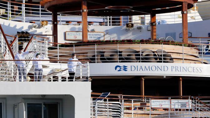 Kru berdiri di geladak kapal pesiar Diamond Princess yang dikarantina di Yokohama, Jepang, Jumat (21/2/2020). Sebanyak 634 dari 3.711 orang kapal pesiar Diamond Princess kini terjangkit virus corona (COVID-19). (AP Photo/Eugene Hoshiko)
