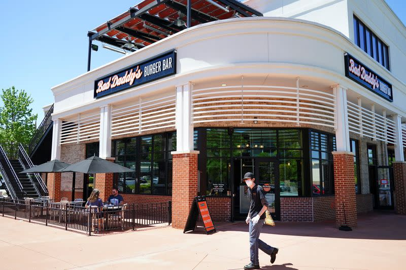 People eat lunch on an outdoor patio at Bad Daddy's Burger Bar as an employee wearing a mask sweeps on the day restaurants and theaters were allowed to reopen to the public, in Smyrna