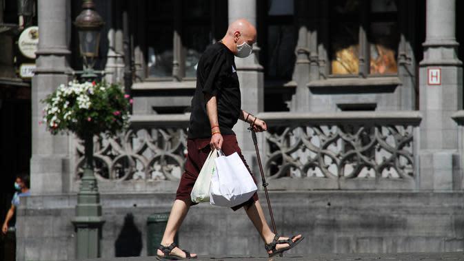 Seorang pria yang mengenakan masker melewati sebuah jalan di Brussel, Belgia (5/8/2020). Kota Brussel memperluas aturan wajib pakai masker di wilayahnya hingga termasuk di jalan-jalan yang ramai dan zona pejalan kaki. (Xinhua/Zheng Huansong)