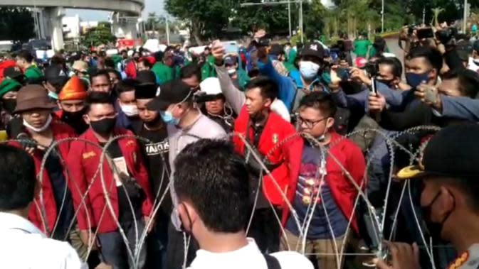 Ratusan massa pendemo yang bernaung di Aliansi Mahasiswa Sumsel melakukan aksi unjuk rasa di simpang lampu merah DPRD Sumsel (Liputan6.com / Nefri Inge)