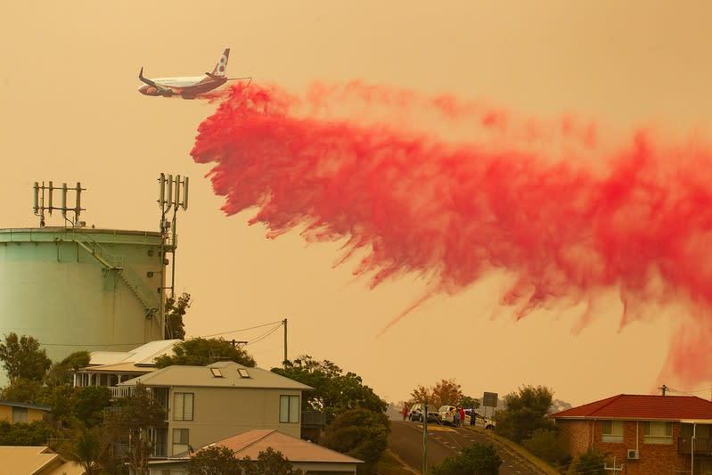 A water bombing plane drops fire retardant on a bushfire in Harrington