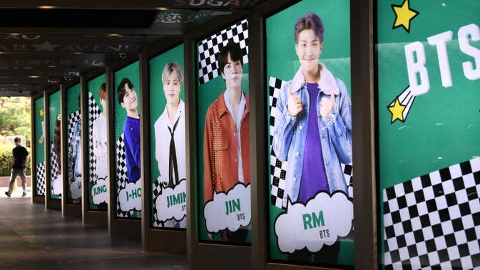Warga melewati poster komersial anggota boyband K-pop, BTS, di luar toko bebas pajak di Seoul, Selasa (1/9/2020). Lagu