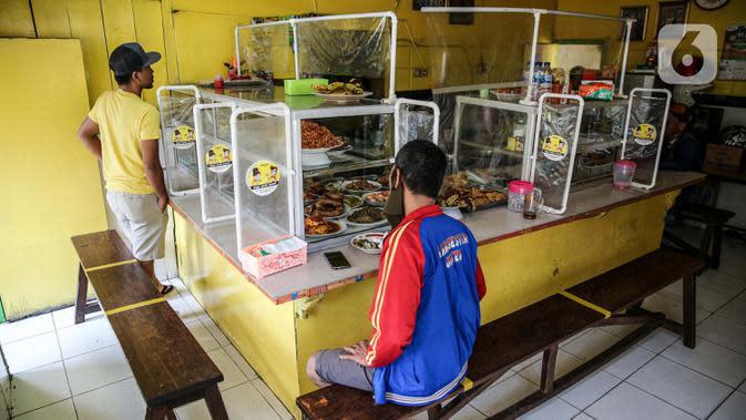 Suasana Warteg Ellya yang menerapkan protokol kesehatan pencegahan penyebaran COVID-19 di Cilandak Timur, Pasar Minggu, Jakarta, Selasa (21/7/2020). Warteg Ellya menerapkan jaga jarak fisik, menyediakan area cuci tangan, mewajibkan pengunjung untuk menggunakan masker. (Liputan6.com/Faizal Fanani)