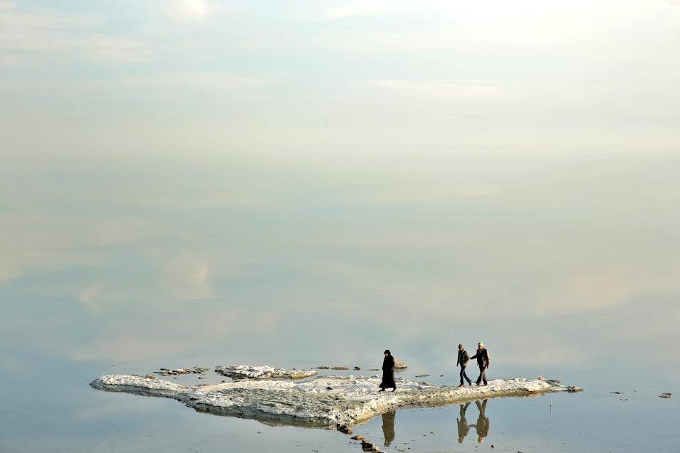 In this Saturday, Feb. 15, 2014 photo, visitors walk on salt-covered rocks that were once deep underwater at Lake Oroumieh Lake, northwestern Iran. Oroumieh, one of the biggest saltwater lakes on Earth, has shrunk more than 80 percent to 1,000 square kilometers (nearly 400 square miles) in the past decade, mainly because of climate change, expanded irrigation for surrounding farms and the damming of rivers that feed the body of water, experts say. (AP Photo/Ebrahim Noroozi)