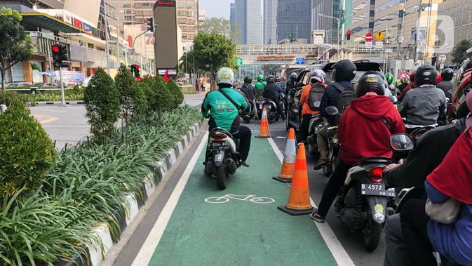 Pengendara motor melintasi lajur sepeda di Jalan MH Thamrin, Jakarta, Selasa (30/6/2020). Untuk menyikapi maraknya penggunaan sepeda sebagai sarana transportasi oleh masyarakat, Kementerian Perhubungan menyiapkan regulasi untuk pesepeda, khususnya aspek keselamatan. (Liputan6.com/Immanuel Antonius)