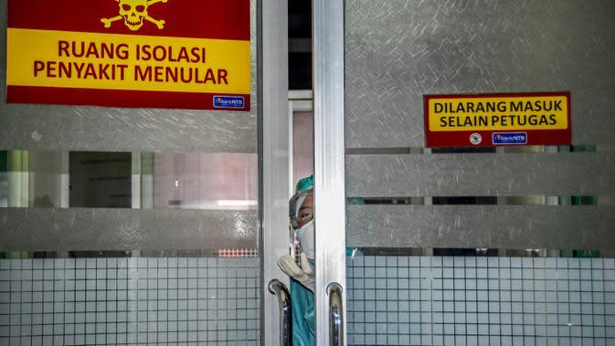 Petugas medis melihat keluar dari ruang isolasi untuk tempat pasien yang menunjukkan gejala wabah virus corona di sebuah rumah sakit umum di Mataram, Nusa Tenggara Barat (28/1/2020). (AFP/Moh El Sasaky)