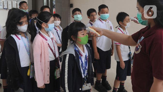 Murid Sekolah Dasar (SD) mendapatkan pemeriksaan suhu tubuh di Jakarta Nanyang School (JNY) di BSD, Tangerang Selatan, Selasa (3/3/2020). Sebelum masuk area sekolah, seluruh siswa wajib menjalani pemeriksaan suhu tubuh untuk mengantisipasi penyebaran virus Corona. (merdeka.com/Arie Basuki)