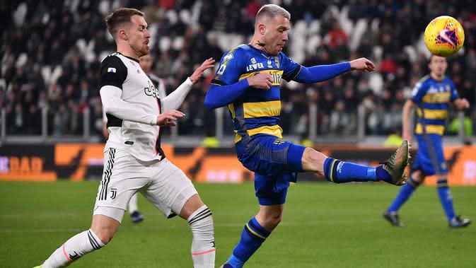 Gelandang Juventus, Aaron Ramsey, berebut bola dengan bek Parma, Simone Iacoponi, pada laga Serie A di Stadion Juventus, Turin, Minggu (19/1). Juventus menang 2-1 atas Parma. (AFP/Marco Bertorello)