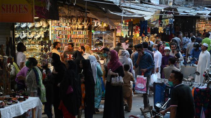 Warga berbelanja jelang Hari Raya Idul Fitri di sebuah pasar di Lahore, Pakistan, Selasa (19/5/2020). Pasar terpantau ramai setelah pemerintah Pakistan melonggarkan lockdown karena pandemi virus corona COVID-19. (Arif ALI/AFP)