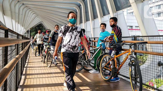 Warga melewati jembatan penyeberangan orang saat berolahraga menggunakan sepeda di sepanjang Jalan Sudirman, Jakarta, Minggu (26/7/2020). Perluasan jalur sepeda sementara dilakukan sebagai dampak peniadaan hari bebas kendaraan bermotor (HBKB) di Jalan Sudirman-Thamrin. (Liputan6.com/Faizal Fanani)