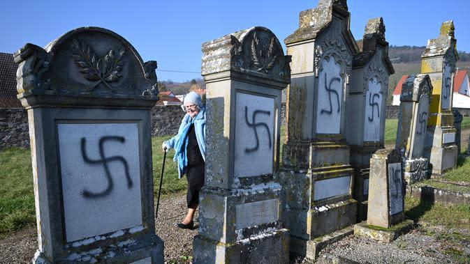 Seorang wanita berjalan di dekat nisan yang menjadi sasaran vandalisme di pemakaman Yahudi, Westhoffen, dekat Strasbourg, Prancis, Rabu (4/12/2019). Sedikitnya 107 makam menjadi sasaran vandalisme dengan dicoreti lambang swastika Nazi. (AFP/Patrick Hertzog)