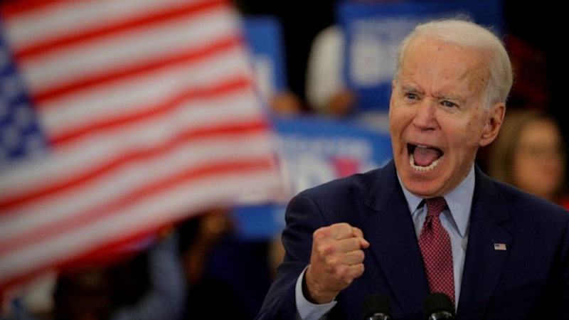 Joe Biden clenching his fist and shouting on stage.