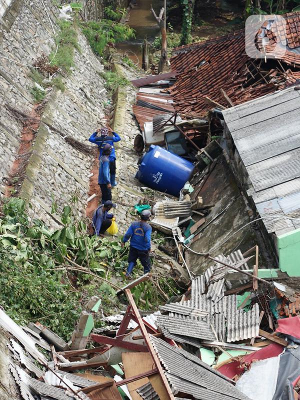 Petugas memeriksa rumah yang hancur akibat longsor di Jalan Damai, Ciganjur, Jakarta Selatan, Minggu (11/10/2020). Hujan yang deras sejak Sabtu (10/10/2020) sore mengakibatkan kawasan tersebut mengalami banjir sekaligus longsor. (Liputan6.com/Immanuel Antonius)