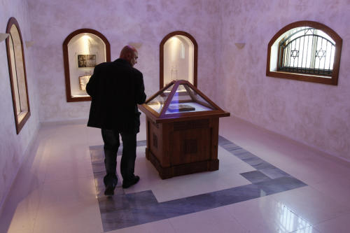 FILE - In this file photo taken on Wednesday, March 31, 2010 Bosnian conservationist technician Hamo Karkelja looks at original book of Sarajevo Haggadah, displayed at the National Museum of Bosnia and Herzegovina in Sarajevo, Bosnia. Officials in charge of Bosnia's national monuments said Wednesday, Feb. 6, 2013 they rejected an offer by New York's Metropolitan Museum of Art to exhibit one of Bosnia's most prized relics, a 600-year-old Jewish manuscript that remains locked in a museum which closed because of a lack of money. ( AP Photo/Amel Emric, File)