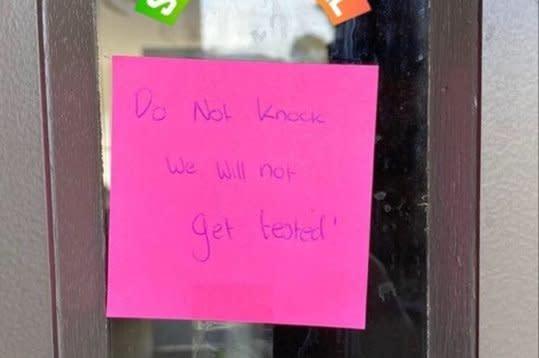 Warga yang menolak didatangi petugas menempelkan pesan di pintu rumah mereka di Melbourne.