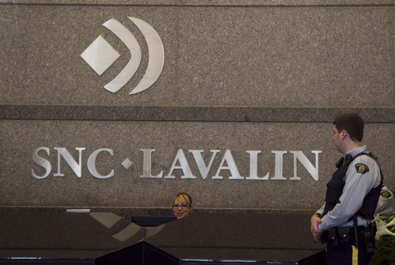 Royal Canadian Mounted Police officer looks at a receptionist at the headquarters of SNC Lavalin in Montreal