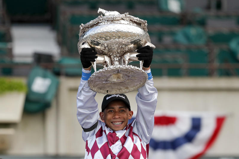 Jockey Manny Franco holds up the August Belmont trophy after riding Tiz the Law to win the 152nd running of the Belmont Stakes horse race, Saturday, June 20, 2020, in Elmont, N.Y. (AP Photo/Seth Wenig)