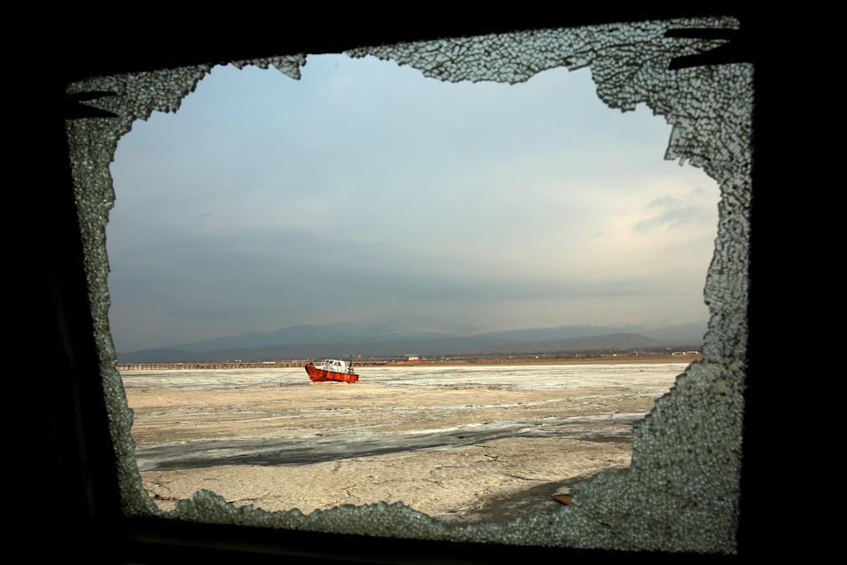 In this Sunday, Feb. 16, 2014 photo, an abandoned boat is seen through the shattered window of an abandoned ship, both stuck in solidified salt at Lake Oroumieh, northwestern Iran. Oroumieh, one of the biggest saltwater lakes on Earth, has shrunk more than 80 percent to 1,000 square kilometers (nearly 400 square miles) in the past decade. Lakes in other parts of Iran are facing a similar crisis, though not as severe as at Oroumieh. (AP Photo/Ebrahim Noroozi)