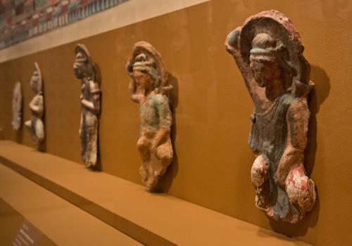 """Bodhisattva holding up as lotus, right, and other sculptures of the Northern Wei Dynasty, 386-534 AD, are displayed in """"Dunhuang: Buddhist Art at the Gateway of the Silk Road,"""" at the China Institute, in New York, Tuesday, April 24, 2013. (AP Photo/Richard Drew)"""