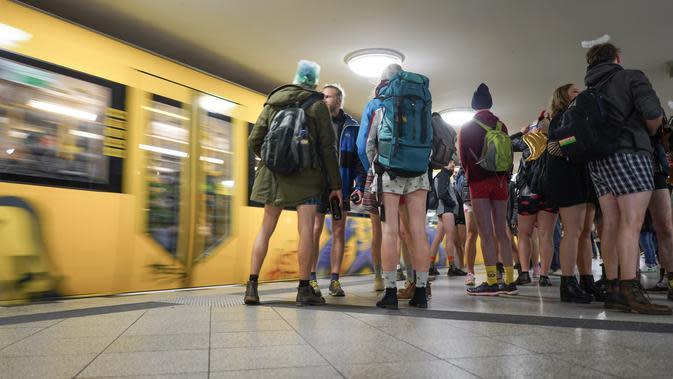 Penumpang tanpa menggunakan celama menunggu kereta di subway selama acara tahunan No Pants Subway Ride di Berlin pada Minggu (12/1/2020). New York menjadi kota pertama yang menghajat acara naik kereta tanpa celana ini sejak tahun 2002. (Jörg Carstensen / dpa / AFP)