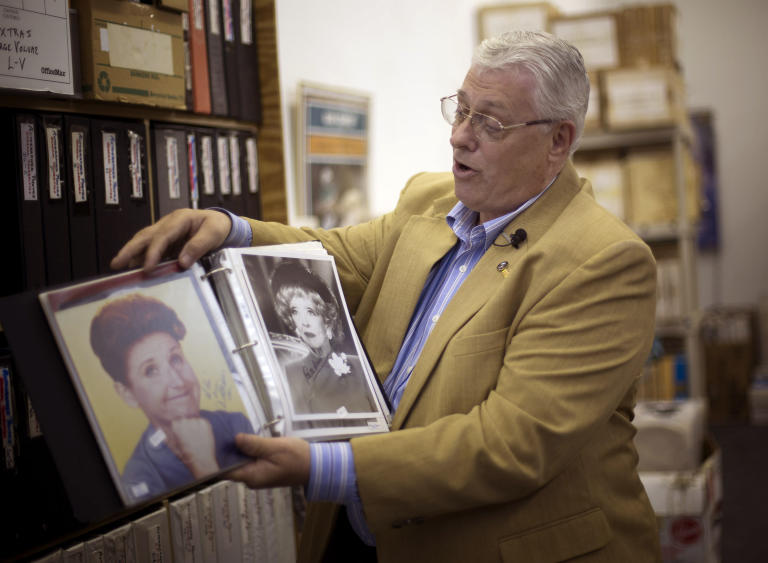 In this Friday, Oct. 19, 2012 photo, memorabilia collector Ken Kallin shows off autographed photos of Ann B. Davis, left, and Betty Davis, at his Oakland Park, Fla. office. Three decades ago, Kallin began amassing 120,000 pieces in a memorabilia collection that includes photographs signed by Muhammad Ali and Neil Armstrong along with rare books and trading cards. By the end of Saturday, Oct. 27, 2012 he's hoping to have gotten rid of nearly all of it _ at an auction to benefit his daughter, who suffers from a rare autoimmune disease that makes her bones dangerously brittle and causes her body's defenses to attack her own blood vessels.  (AP Photo/J Pat Carter)