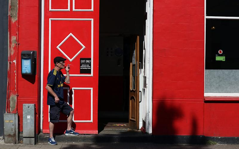 LONDON, ENGLAND - JULY 12: A fan in an Arsenal shirt leaves The Corner Flag pub through an Exit Only door so he can smoke a cigarette during the Premier League match between Tottenham Hotspur and Arsenal FC at on July 12, 2020 in London, United Kingdom. Football Stadiums around Europe remain empty due to the Coronavirus Pandemic as Government social distancing laws prohibit fans inside venues resulting in all fixtures being played behind closed doors. (Photo by Charlotte Wilson/Offside/Offside via Getty Images) - Charlotte Wilson/Offside via Getty Images