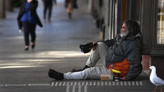 Seorang pria meminta uang di kawasan pusat bisnis Melbourne pada Rabu (2/9/2020). Australia memasuki resesi pertama mereka sejak 1991 setelah perekonomian menyusut 7,0 persen pada kuarter kedua saat negara itu berjuang menghadapi pandemi COVID-19. (William WEST / AFP)