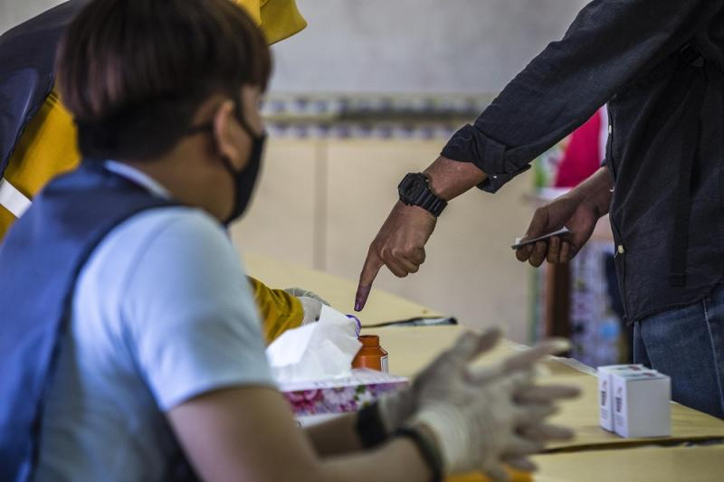A voter gets his finger marked with indelible ink at the voting station located at SK Pulau Gaya September 26, 2020. — Picture by Firdaus Latif