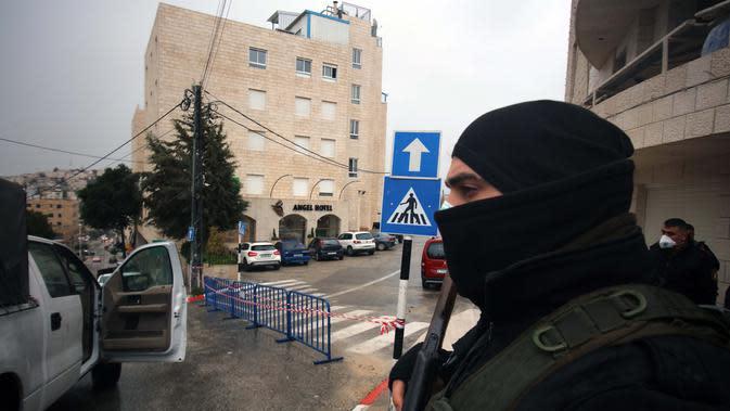 Dengan mengenakan masker, seorang aparat kepolisian Palestina berjaga-jaga di luar Angel Hotel di Kota Betlehem, Tepi Barat, pada 6 Maret 2020. Keadaan darurat mulai diberlakukan pada Jumat (6/3) di Palestina di tengah kekhawatiran penyebaran coronavirus baru. (Xinhua/Stringer)