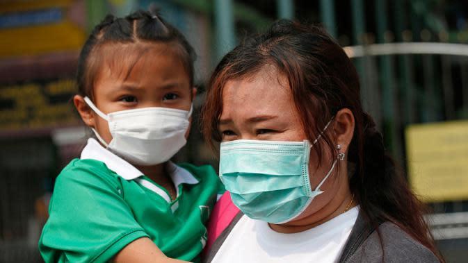 Seorang anak perempuan mengenakan masker saat dijemput orang tuanya di Bangkok, Thailand (30/1). Partikel PM 2,5 terus meningkat di atas ambang batas aman yang ditetapkan WHO yaitu 50 mikrogram per meter kubik. (AP Photo/Sakchai Lalit)