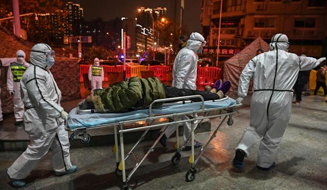 Medical staff members wearing protective clothing arrive with a patient at the Wuhan Red Cross Hospital on Saturday. Photo: AFP