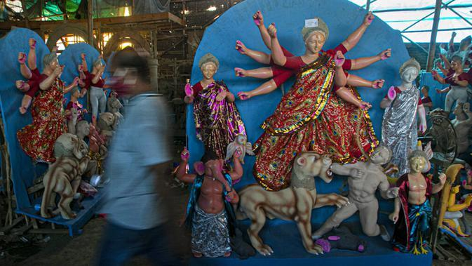Seniman berjalan melewati patung Dewi Durga jelang Festival Durga Puja di Gauhati, India, Jumat (16/10/2020). Para pejabat kesehatan memperingatkan tentang potensi penyebaran COVID-19 selama musim festival keagamaan dengan pertemuan besar di kuil dan distrik perbelanjaan. (AP Photo/Anupam Nath)
