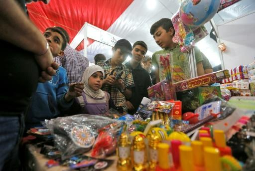 "Syrian children browse merchandise as they attend the government-sponsored ""Ghouta Shopping Festival"" on May 13, 2018"