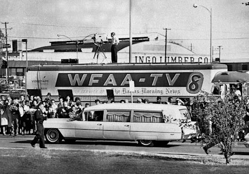 FILE - In this Nov. 22, 1963 file photo, people line the street as the hearse bearing the body of slain U.S. President John F. Kennedy drives past a television truck as it leaves Parkland Hospital in Dallas, to be flown to Washington. (AP Photo/File)