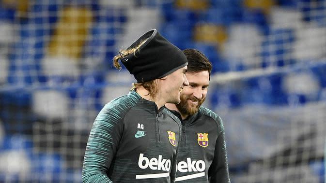 Penyerang Barcelona, Lionel Messi (kanan) berbincang dengan Antoine Griezmann saat menghadiri sesi pelatihan di stadion San Paolo di Naples, Italia (24/2/2020). Barcelona akan bertanding melawan Napoli pada leg pertama babak 16 besar Liga Champions. (AFP/Filippo Monteforte)