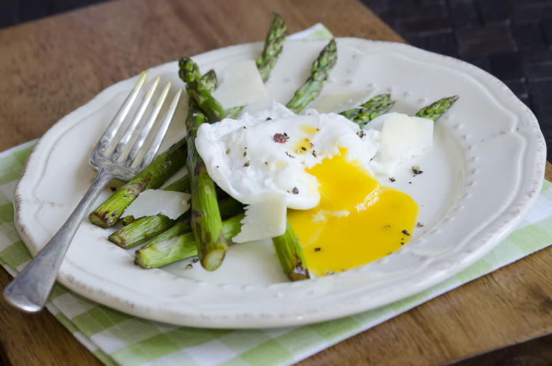 Grilled asparagus with poached eggs and parmesan shavings is another delicious way to eat the vegetable. (Getty Images)