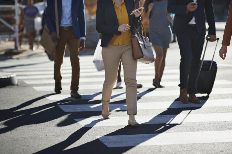 A file image of pedestrians crossing the road at a zebra crossing using their phones. NRMA has found more than a third of pedestrians are distracted.