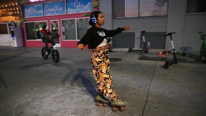 Seorang pengguna sepatu roda melintasi trotoar Venice Beach di Venice, California, Kamis (3/9/2020). Menurut data Google, pencarian terkait sepatu roda dari Maret hingga Mei di Amerika Serikat meningkat hampir empat kali lipat. (Mario Tama/Getty Images/AFP)
