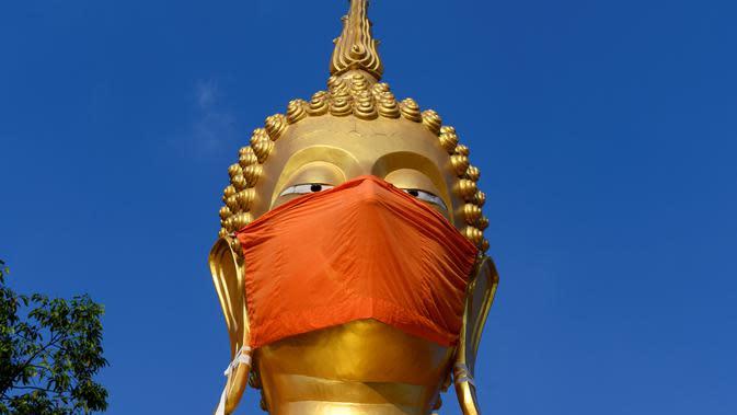Masker diletakkan pada wajah patung Buddha raksasa di kuil Wat Nithet Rat Pradit di Pathum Thani di luar Bangkok, Thailand, 12 Mei 2020. Pemasangan masker tersebut sebagai tanggapan terhadap penyebaran pandemi Covid-19. (Photo by Mladen ANTONOV / AFP)